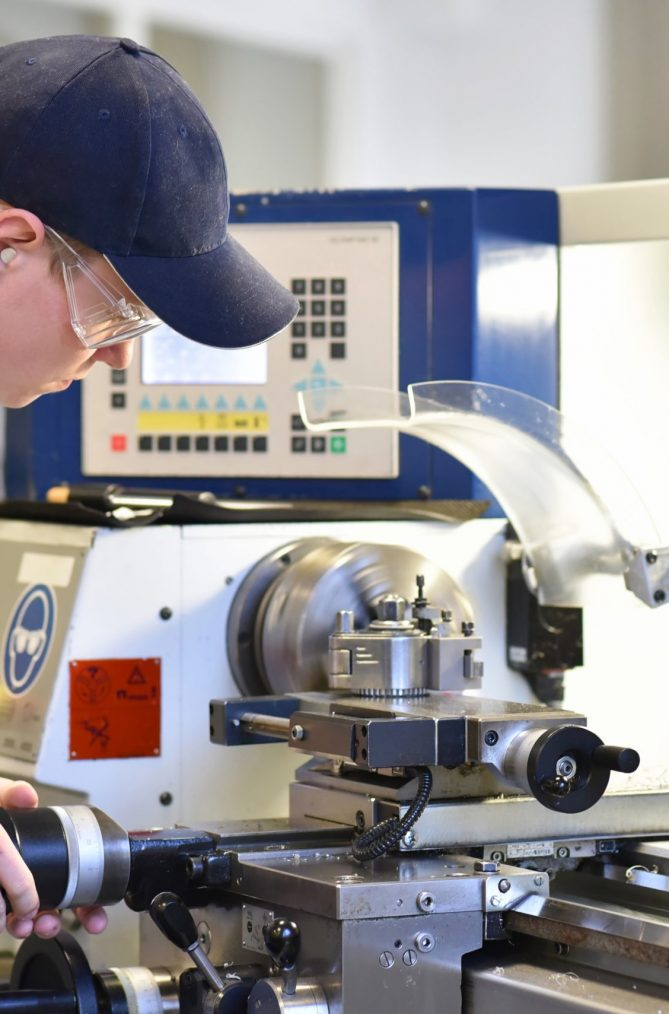 young apprentice in vocational training working on a turning machine in the industry
